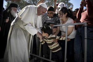 A boy shakes the hand of Pope Francis as he greets migrants and refugees at Moria refugee camp near the port of Mytilene, on the Greek island of Lesbos in this handout photo released by the Greek Prime Minister's press office, April 16, 2016. REUTERS/Andrea Bonetti/Greek PM Press Office/Handout via Reuters